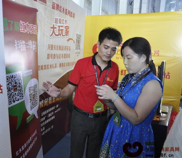"""中国古典家具网、《品牌红木》杂志工作人员正在协助参展者参加""""超级红木大玩家""""活动"""
