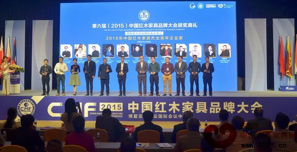 """两木品牌创始人林锐群荣获""""2015年中国红木家具杰出青年企业家""""称号,企业代表上台接受颁奖"""