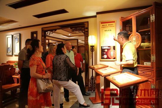 志成红木总经理汤朝阳(右一)为外国友人们详细介绍志成红木智能家具锁工艺特点