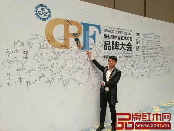 博大家具受邀出席第七届中国红木家具品牌大会,总裁助理廖柱平在签到板前签字留念