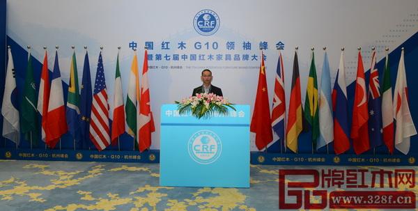 林木轩董事长朱南雄在第七届中国红木G10领袖峰会纪念板前合影留念