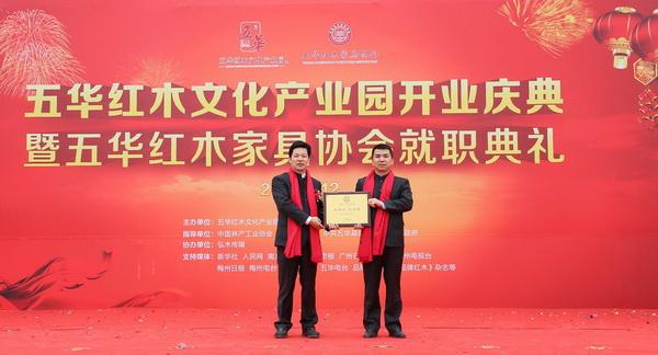 五华红木家具协会会长张锡复(左)为五华红木家具协会秘书长张利春颁牌