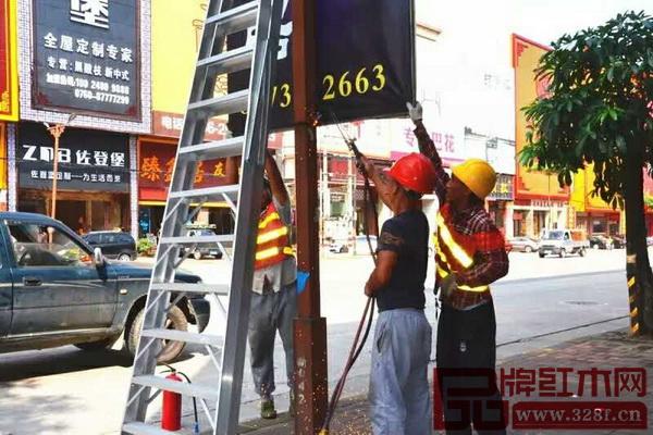 城管执法人员在中山市大涌镇红木企业集聚路段拆除违规灯旗广告