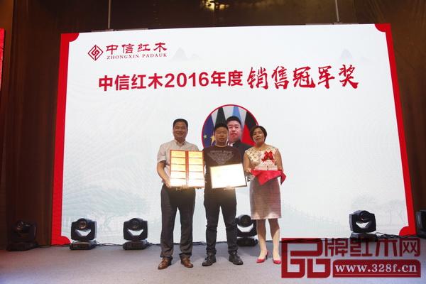 中信红木董事长李忠信(左一)及其夫人(右一)为2016年度销售冠军李良专(中)颁发奖牌及四十万现金和十块金钞的奖励