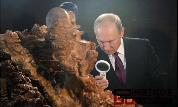 普京正拿着放大镜细细观赏精致木雕