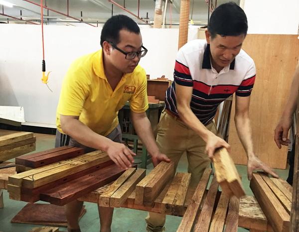 区氏臻品董事长区胜春(右)与工匠一同严把黄花梨选料