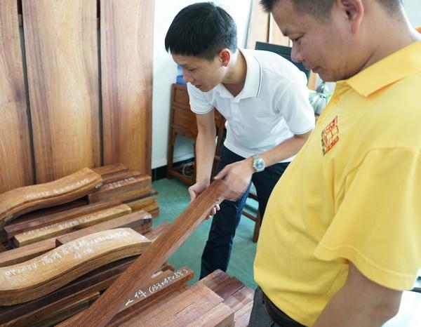 区氏臻品总经理区锦泽(左)与工匠一同严把黄花梨选料