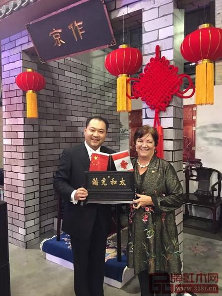"""太和木作董事长关毅先生(左)向加拿大前副总理希拉·科普斯女士赠送""""太和充满""""故宫微型匾额"""