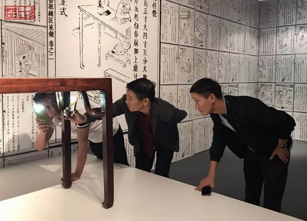 区氏臻品董事长区胜春(右二)、总经理区锦泽(右一)用手机电筒在看家具