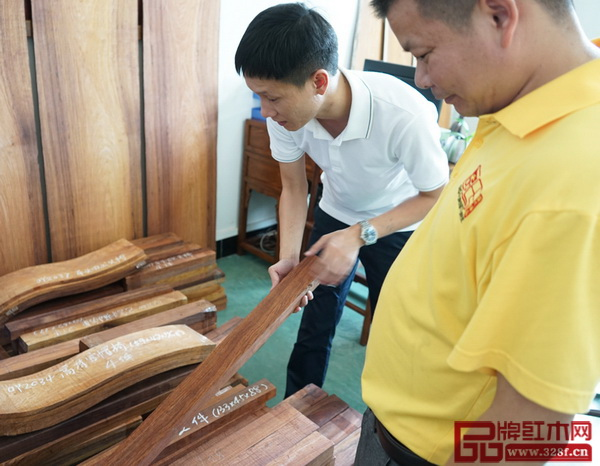 区氏臻品总经理区锦泽与工匠一起检查黄花梨的开料情况