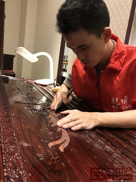 龙博士家具工匠正在专心致志的进行雕刻