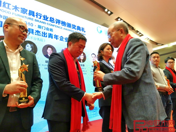 中国红木家具技术专家曹新民为大汇堂董事长胡春龙颁发杰出青年企业家奖杯