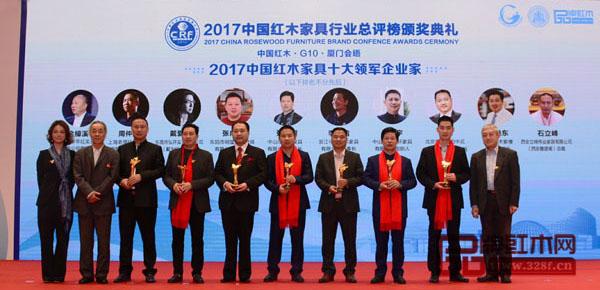 """戴为红木总裁戴爱国(左一为董事总经理翁肖尤代领)被授予""""2017年中国红木家具十大领军企业家""""称号"""