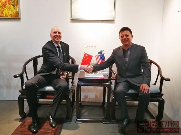 洛杉矶艺博会创始人KimMartindale(左)与中国传统工艺大师、明堂红木创始人张向荣落坐明堂红木《首席椅》