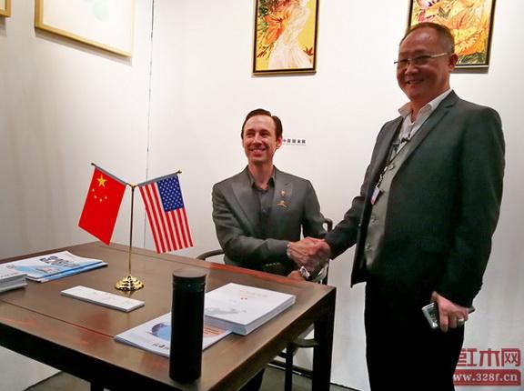 美国洛杉矶国际艺术博览会董事局主席斯科特(左)落坐《背板云纹开光南官帽椅》并与中国传统工艺大师、鲁班木艺董事长李爱金(右)合影留念