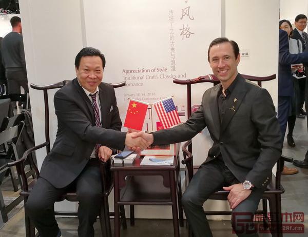 美国洛杉矶国际艺术博览会董事局主席斯科特(右)与中华高级木作师、红宝轩董事长曹兆庭(左)坐于《大明雅韵·辉煌腾达官帽椅》合影留念