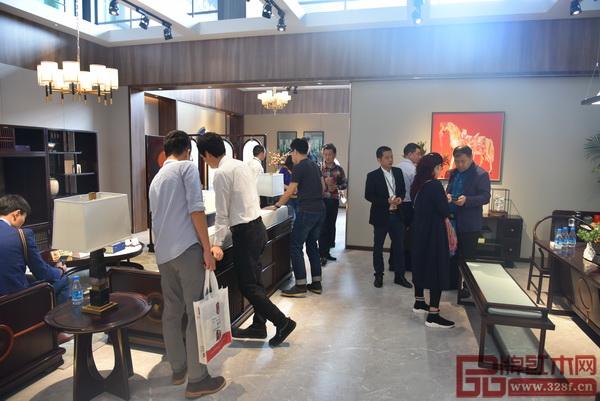 东成红木工作人员在给家居爱好者介绍家具