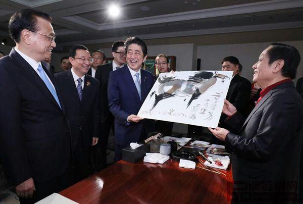 故宫文创展上,众人围绕纯本森活画案正在欣赏北京奥运会吉祥物福娃设计者韩美林(右一)画作