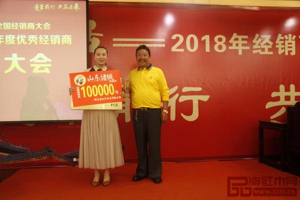 在明清居2017优秀经销商表彰大会上,董事长金彪云(右)为获奖经销商颁奖