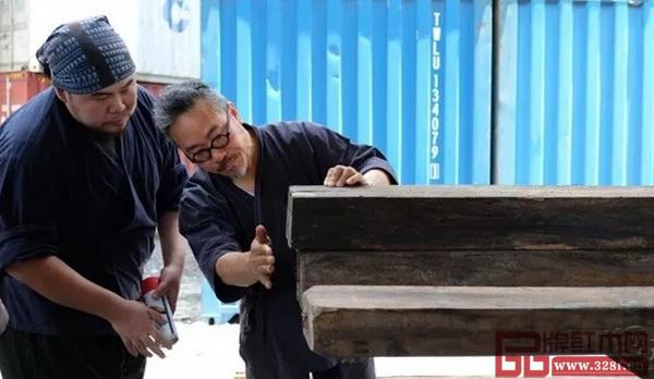何兆基(右)与林昆佑在物流中心堆放着大量红木木材的船运货柜旁挑选木材(图片来源:南华早报)