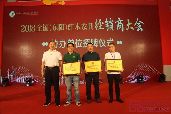 兴成红木(右二)接受2018全国(东阳)红木家具经销商大会协办单位颁牌
