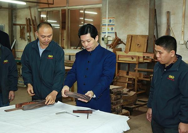 中国传统工艺大师,东成红木董事长张锡复(右二)经常与团队就红木家具制造分析查找原因,提出具体的改进意见