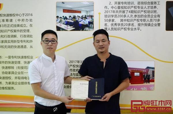 中山市红木家具行业协会秘书长林毅昭(左)为厉国阳颁发版权证书