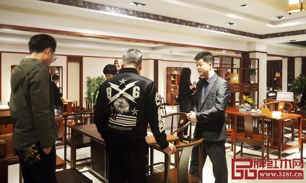 水雨轩企业代表宋献政(右一)向经销商介绍功夫茶台