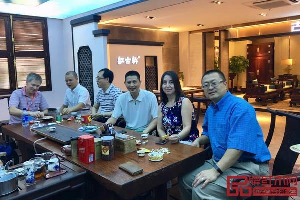 美国客人与红古轩总经理吴赤宇(右三)坐在中式茶台前聊天