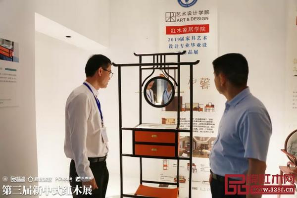 """贺修虎(右一)参观""""新意思""""新中式红木家具设计展展区"""