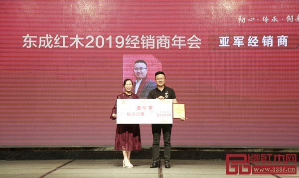 东成红木副董事长林霞(左)为东成红木2018年度销售亚军经销商颁奖
