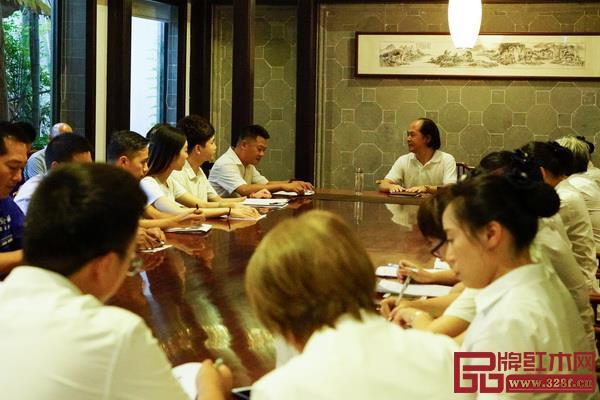 """中国木雕艺术大师、大清翰林董事长吴腾飞(中)与员工们一起探讨、分享""""八德""""文化"""