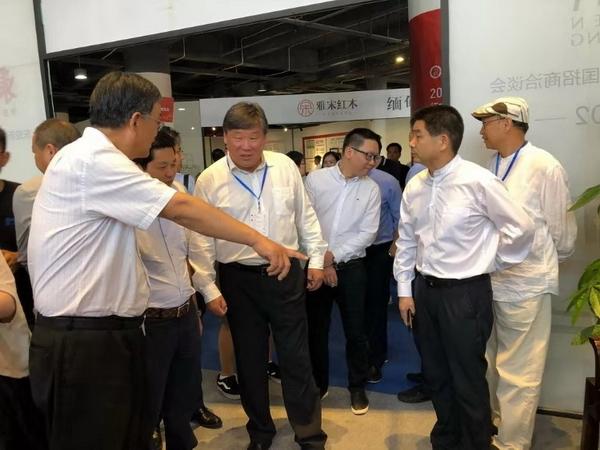 中国林业产业联合会副会长、北京林业大学原校长宋维明(左三)对东成红木的展出作品赞誉有加