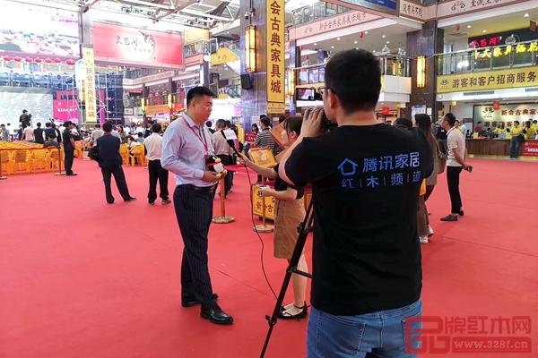 居典红木董事长尹付林正接受腾讯家居与品牌红木的现场采访