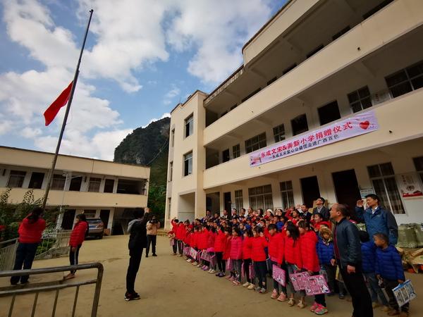穿上了新棉衣、领到了新文具的同学们,和东成红木爱心助学公益团一起进行升旗仪式