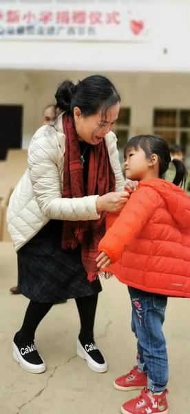 东成红木副董事长林霞为孩子们穿上温暖的棉衣