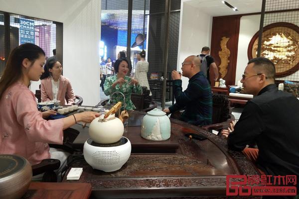 红星美凯龙控股集团有限公司联席董事长车建芳(左三)与卓木王红木总裁杜长江(右二)在展厅内深入沟通