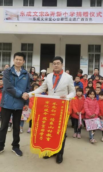 凌云县浩坤村驻村书记刘栋明(左)为东成红木赠送锦旗