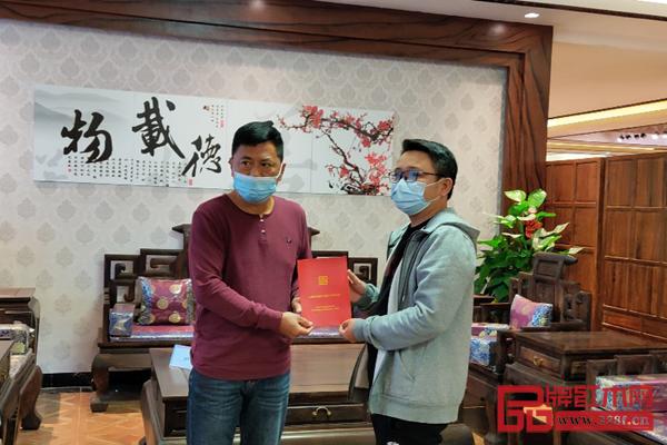 中國紅木消費權益保障工程(廣東)副主任鄧欽昌(左)與家具購買者葉先生(右)在購買的家具前合照