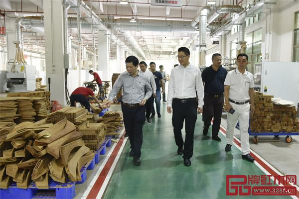 广东省家具协会会长王克(左二)在东成红木董事长张锡复(左一)的陪同下,参观五华红木家居产业园东成红木智能化工厂