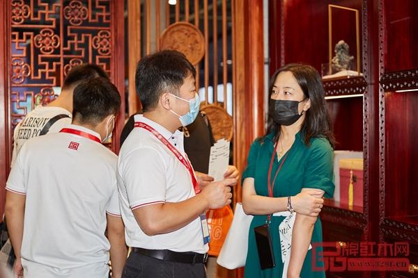 国方家居顾问在为参展商介绍国方家居中式原木整装特色